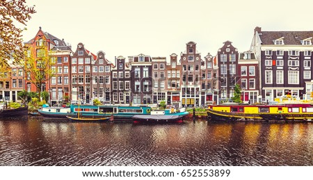 Dancing house in Amsterdam Netherlands over river Amstel panorama of traditional Dutch architecture with boat on bank urban landscape.