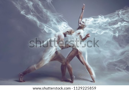 Dancing in flour. Naked couple in love in dust / fog. Girl and guy dancers wearing white sport clothing dancing in flour cloud on isolated background. Surreal concept.