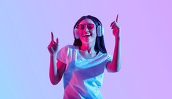 Dancing in modern wireless headphones. Asian girl with glasses enjoys favorite song, isolated in neon, studio shot