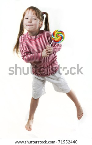 dancing little girl eats a lollipop isolated on white