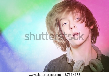 dancing male teenager with headphones and disco background.