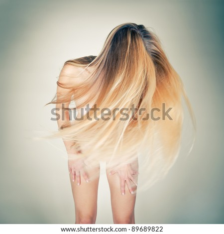 Dancing nude woman shacking her long blond hair, toned photo