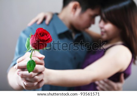 Dancing romantic lovers with a rose in hand.Narrow depth of field.