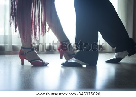Dancing shoes feet and legs of female and male couple ballroom and latin salsa dancer dance teacher in dance school rehearsal room class. #345975020