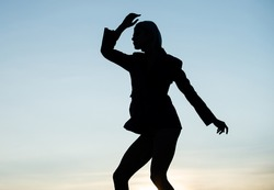 Dancing silhouette of dance girl woman dancer in dusk silhouetted on evening sky, performer