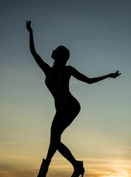 Dancing silhouette of woman ballet dancer in twilight silhouetted on evening sky, ballet