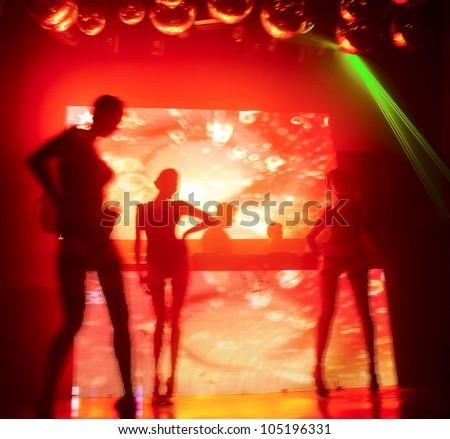 Dancing silhouettes of woman in nightclub. Bright beautiful rays of light