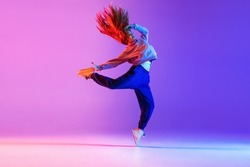 Dancing style. Young beautiful girl expressively making hip-hop tricks on gradient neon background. Youth culture, style and fashion. Concept of dance, youth, hobby, dynamics, movement, action, ad