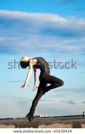 dancing woman in modern pilates style over urban city landscape and blue sky. Yoga