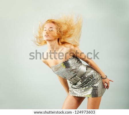 Dancing Woman in Silver Dress. Fashion Photo