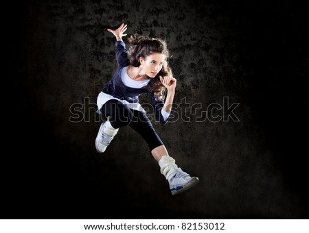 Dancing woman with brown long hair and happy facial expression jumping up.