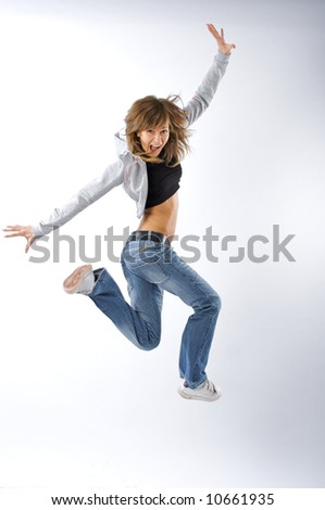 Dancing woman with brown long hair and happy smiling facial expression jumping up.