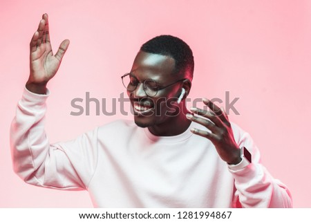 Dancing young african man listening to music with earphones isolated on pink background