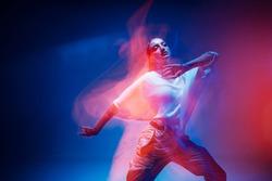 Dancing young mixed race girl enjoying moving in colorful neon studio light. Long exposure. Ethnic fiery dance