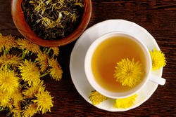 Dandelion tea with a fresh yellow flower inside a cup, on wooden background. Vitamin drink. Dandelion herbal tea for health.