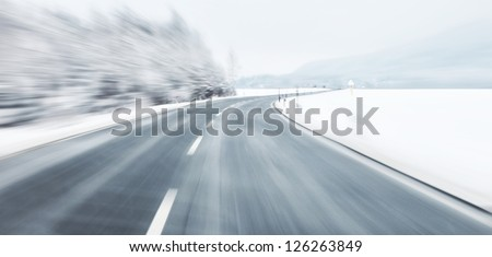 Danger and fast turn at the icy snow road. Motion blur visualizies the speed and dynamics.