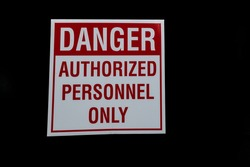 Danger authorized personnel only sign red letters on white with all black background