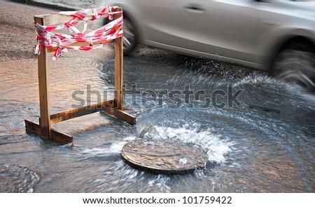 Danger border near water leak on the road - stock photo