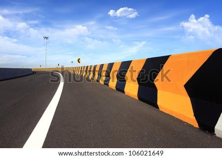 danger curve road sign with blue sky
