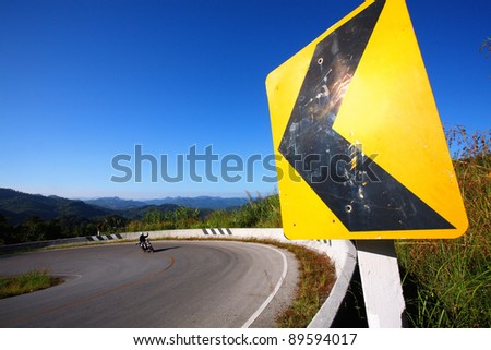 danger curve road sign with blue sky