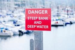 Danger deep water and steep bank at sea harbour marina