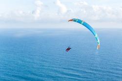 Danger extreme flying tandem paraglider over the sea