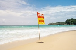 Danger for swimming red flag on beach.Caution sign that tourists  on the beach.Landscape clean sea white clouds soft daylight.Blue sea waves and sky on sand beach.