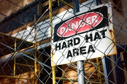 Danger hard hat area safety warning sign on a chain link fence at a house construction work site