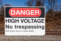 Danger, high voltage, no trespassing sign on a fence in front of a rail road. It lists possible health hazards including shock, trauma and death underneath. Train tracks seen blurred in background.