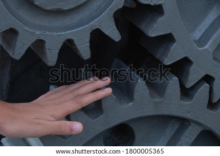 Photo of  danger of a hand caught in the gears of a moving machine concept danger