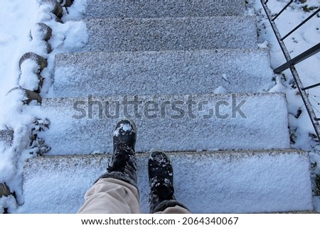 Danger of accident on snow-covered slippery steps of stairs in winter
