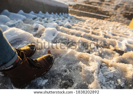 Danger of slipping. Female boots on rough slipper ice surface. A woman in brown leather shoes descends the slippery ice ladder. Stock photo ©