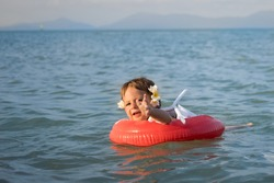 danger on vacation. adorable toddler toddler swims alone unattended in the sea in a special inflatable ring