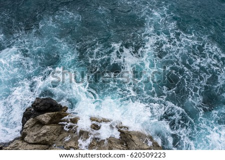 Danger sea wave crashing on rock coast with spray and foam before storm in Positano, Italy #620509223