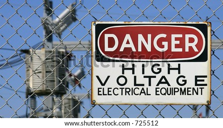 Danger Sign hanging on a fence. White, black and red sign warning of electrical hazard