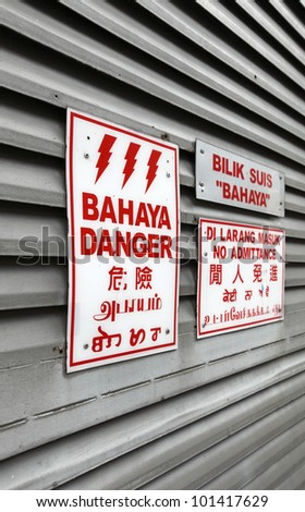 Danger sign panel in four languages, English, Bahasa Indonesia, Chinese and Hindi on a metal louver door.