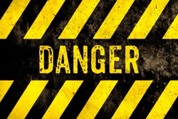 Danger warning sign text with yellow and black stripes painted over concrete wall surface facade texture background. Concept image for caution, dangerous area and hazard.