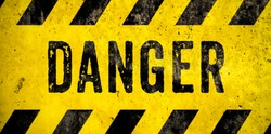 DANGER warning sign word text as stencil with yellow and black stripes painted over concrete wall cement texture wide banner background. Concept image for caution, dangerous area and hazard.