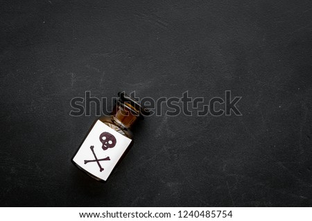 Dangerous addictions, dangerous entertainment. Poison. Bottle with skull and crossbones on black background top view space for text