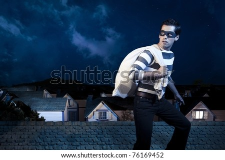 dangerous burglar about to enter house - stock photo