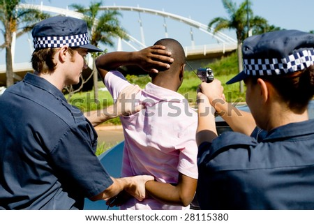 dangerous criminal under arrest at gun point - stock photo