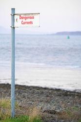 Dangerous currents at sea sign under bridge