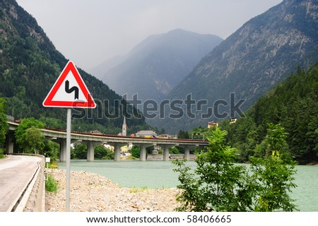 Dangerous Curves Sign At The Road Along Adige River in The Alps