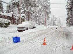 Dangerous downed power lines during a winter storm. Power lines are on top of a snowed in car and on the snow covered street. A car is approaching. Traffic cones are placed around the area.