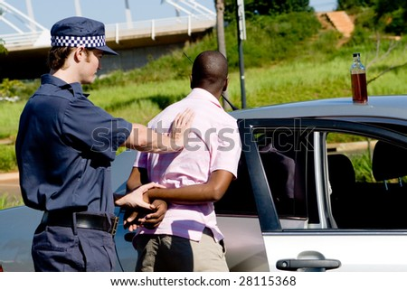 dangerous drunk driver been arrested by policeman, a bottle of wine still on the car