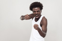 Dangerous fighter. Afro man ready to fight. Studio shot. Gray background