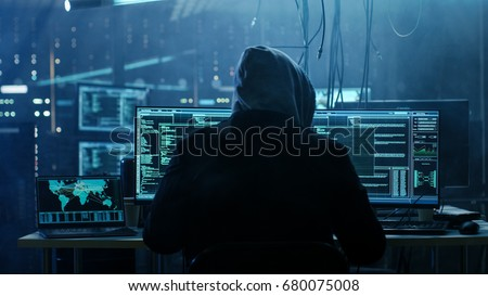 Dangerous Hooded Hacker Breaks into Government Data Servers and Infects Their System with a  Virus. His Hideout Place has Dark Atmosphere, Multiple Displays, Cables Everywhere. Stock photo ©