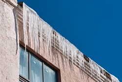 Dangerous icicles melt on rooftop, risk of injury. Sharp icicles hanging down from roof of residential building against sunny background. Transparent icicle on facade of building