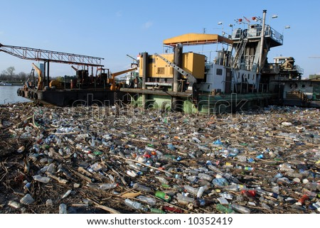 Dangerous industrial toxic garbage floating in river with other pollute waste