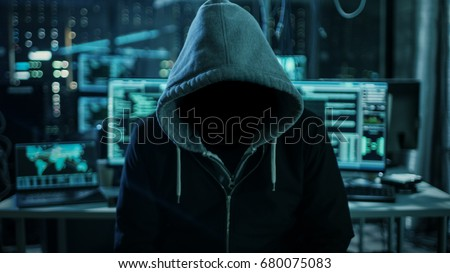 Dangerous Internationally Wanted Hacker Wth Hided Face Looking into the Camera. In the Background His Dark Operating Room with Multiple Displays and Cables.